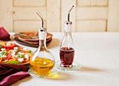 Je eine Karaffe Olivenöl und Essig, auf weißem Tischtuch mit Pizza im Hintergrund
