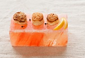 Three Scallops with Pepper and Lemon on a Pink Himalayan Salt Block