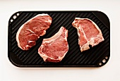 Three Raw Steaks on a Grill Pan; From Above on a White Background