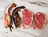 Surf and Turf; Raw Lobster and Steaks on Marble