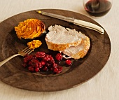 Serving of Sliced Roasted Turkey, Cranberry Sauce and Sweet Potatoes; On a Wooden Plate; With Wine