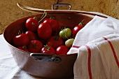 Tomatoes in a copper bowl with a tea towel and a wooden spoon