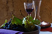 A bowl of red and green grapes in front of a decanter and a glass of red wine