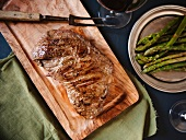 Garlic Herb Sirloin on a Cutting Board; Platter of Asparagus; From Above