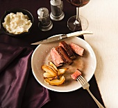 Sliced Steak and Onions in a Plate; Piece of Steak Pierced on a Fork; Side of Mashed Potatoes and Red Wine