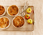 Individual Apple Cobblers on a Tray with Spoons and Apples