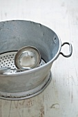 An old kitchen colander and a ladle