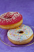 Two doughnuts with glaze and sugar sprinkles