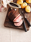 Roast beef with a Port wine sauce and roast potatoes on a wooden board