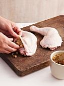 A chicken leg being stuffed under the skin