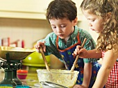 Children stirring a bowl of cake mixture
