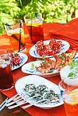 A table laid with snails, prawns, tomatoes and aperitifs