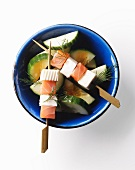 Salmon and feta kebabs on a bed of cucumber slices