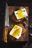 Two wholemeal rolls topped with cottage cheese and honey on a wooden board with a knife