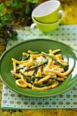 Corn noodles with asparagus on a green plate