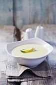 Cream horseradish soup in a white bowl on a grey napkin