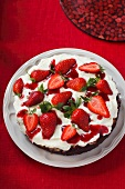 A cream cake with dark base topped with strawberries on a table with a red cloth