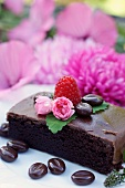 A slice of chocolate cake decorated with chocolate coffee beans and flowers