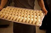 Person hält Backblech mit ungebackenen Croissants