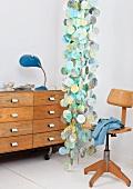 Retro Drehstuhl aus Holz neben Dekoobjekt von Decke abgehängt aus farbigen aufgefädelten Plättchen und Schubladenschrank auf Rollen