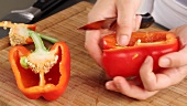Halving and deseeding a red pepper