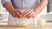 Flour being sieved into a bowl and salt and an egg being added