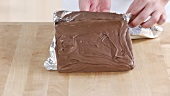 Chocolate fudge being removed from the baking tin and the aluminium foil being removed