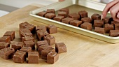Chocolate fudge being placed on baking tray