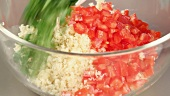 Ingredients for tabbouleh being placed in a bowl (close-up)
