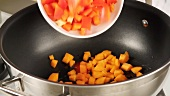 Carrots and pepper being added to a pan of hot oil