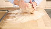 Bread dough being shaped into a loaf on a floured work surface