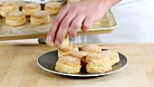 Freshly baked buttermilk biscuits being placed on a plate