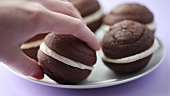 A hand taking a chocolate whoopie pie from a plate