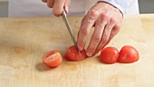 The peeled tomatoes being quartered