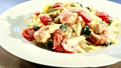 Ribbon pasta with prawns and cream sauce arranged on a plate