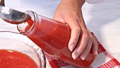 Home-made tomato juice being spooned into a bottle