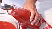 Selbst gemachten Tomatensaft in eine Flasche füllen