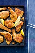 Baked chicken pieces with lemon wedges on a baking tray