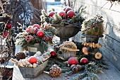 Weihnachtliches Terrassen-Arrangement mit gefrorenen Rosen, Zweigen und Kieferzapfen