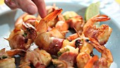 Prawns wrapped in bacon on a plate with a hand reaching for one