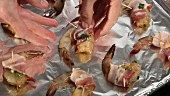 Prawns wrapped in bacon being placed on a baking tray lined with aluminium foil