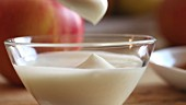 Natural yoghurt being stirred in a glass bowl