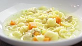 Chicken noodle soup in a plate (close-up)