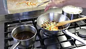 Bolognese sauce being made: diced vegetables being added to minced meat