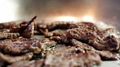 Strips of beef being fried (close-up)