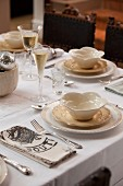 Festively set table with champagne flutes & cream crockery