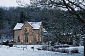 Blick über einen verschneiten Bachlauf auf das abendlich beleuchtete Verwalterhaus eines englischen Anwesens