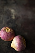 Two turnips on a dark surface