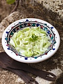 Cucumber salad with parsley on a stone wall