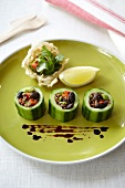 Steamed cucumber slices with soya mince filling, served on a green plate with fried rice noodles with coriander